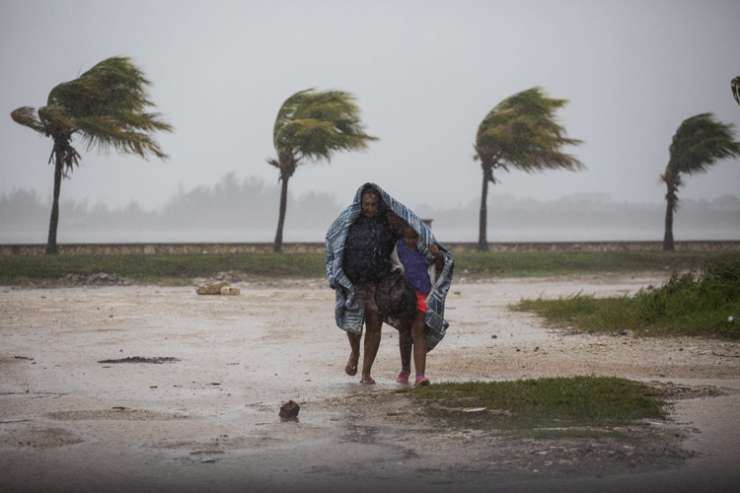 India Tv - Woman and child walk in wind and rain in Caibarien, Cuba