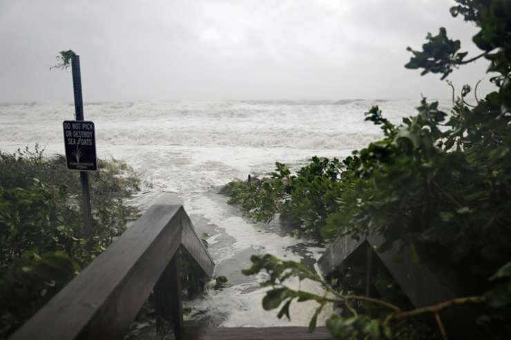 India Tv - The surf floods a walkway leading to the beach in Naples, Florida