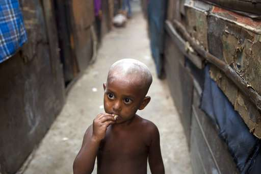 A Rohingya Muslim boy eats candy at a camp for refugees in New Delhi