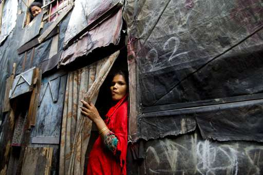A Rohingya Muslim woman stands by the entrance to her shanty at a camp in Delhi