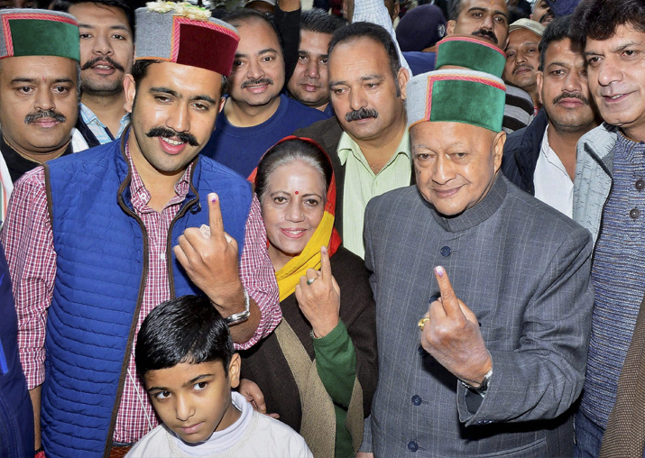 Virbhadra Singh with wife Partibha Singh and son Vikrmaditya Singh showing their inked finger after they cast their vote at a polling booth in Rampur