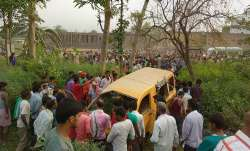 People gather around the mangled school van after it