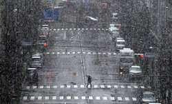 A woman walks in falling snow in Tokyo Saturday, March 28, 2020. Tokyo Gov. Yuriko Koike has repeate
