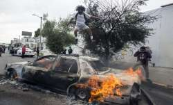 Tear gas and burning cars in US cities as unrest continues