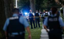 Chicago police officers investigate the scene of a deadly shooting where a 7-year-old girl and a man