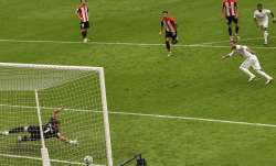 Real Madrid's Sergio Ramos, right, scores the opening goal
