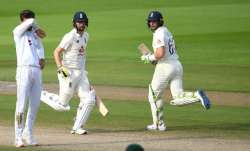 Jos Buttler and Chris Woakes of England run watched on by