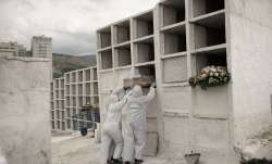 In this Sept. 24, 2020, file photo, cemetery workers place the coffin containing the remains of Jose