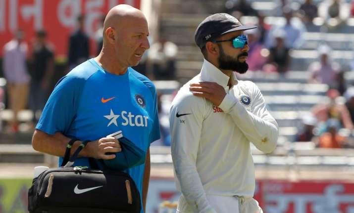 Virat Kohli walks off the field after suffering shoulder