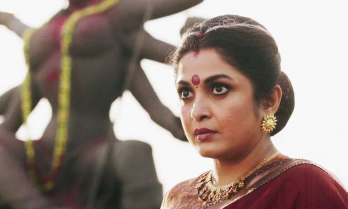 A brown woman with heavy eye makeup stares challengingly ahead. She wears a red sari and heavy gold jewelry.
