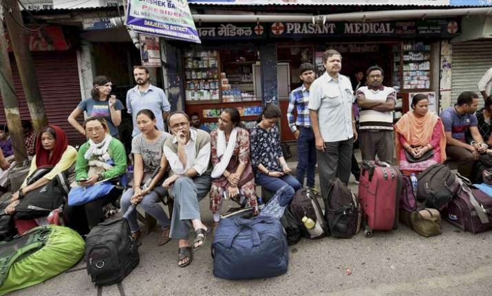Stranded tourists wait at a bus stand in Darjeeling