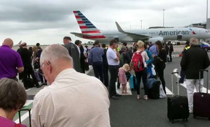 Passengers stand on the tarmac after being evacuated at