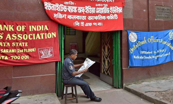 A security guard reads a newspaper in front of a closed