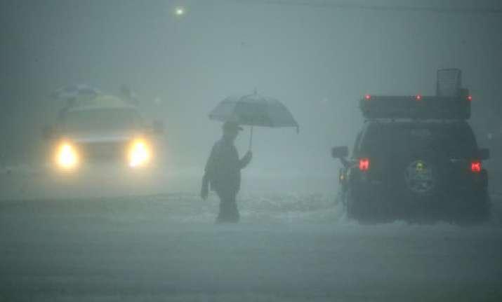 A man walks in heavy rain in Houston, Texas on Aug 27