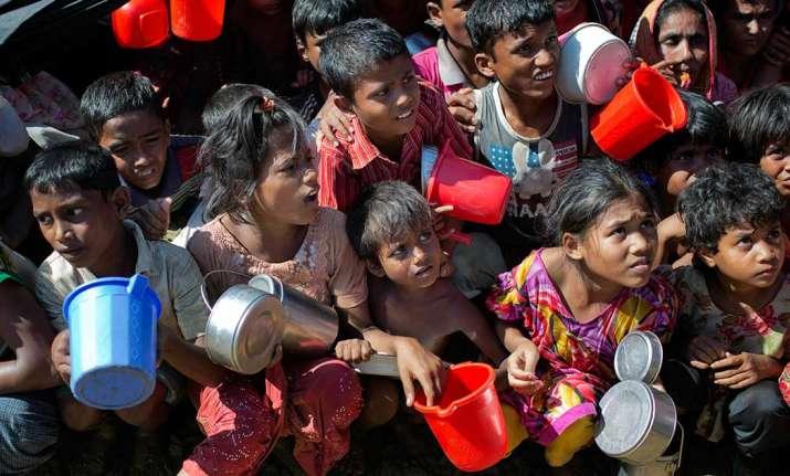 Rohingya Muslim children wait to receive food handouts at
