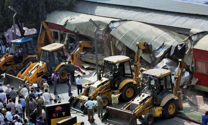 Onlookers gather around as BMC bulldozers take down