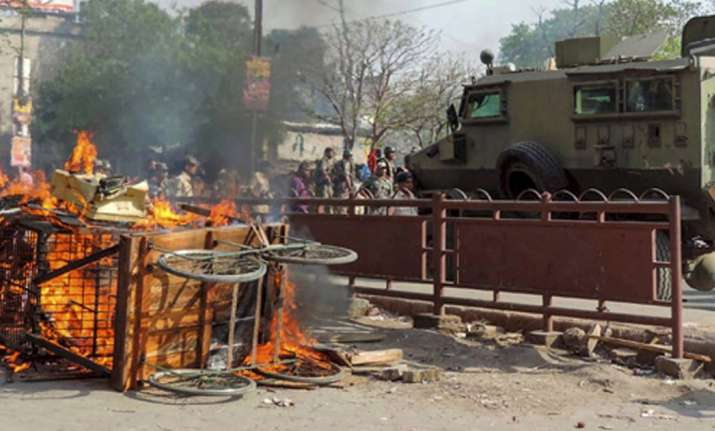 A cart set ablaze in violent clashes between two groups