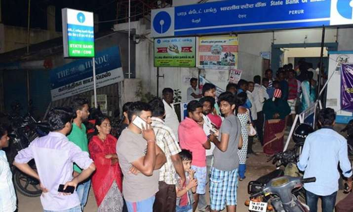 People waiting for their turn outside an ATM to withdraw
