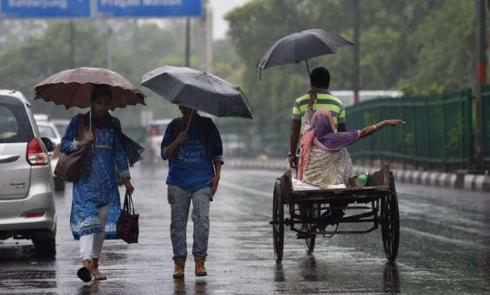 Commuters cross a road during a rainfall, in New Delhi, on