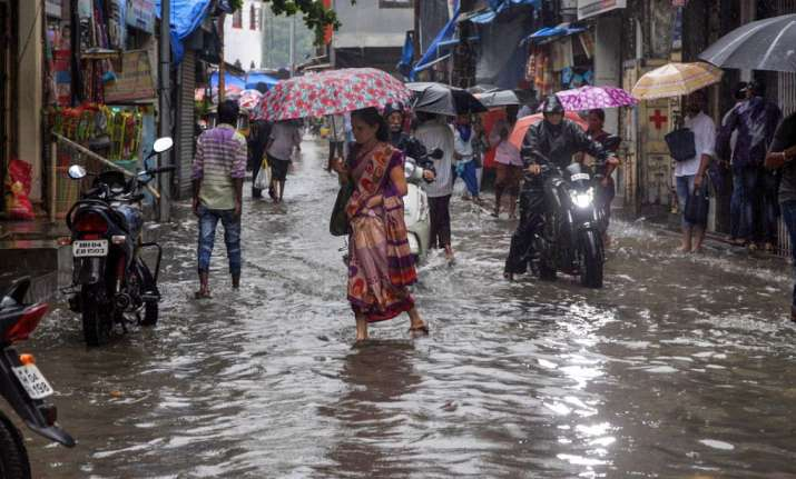 Thane: People walk through a water-logged street after