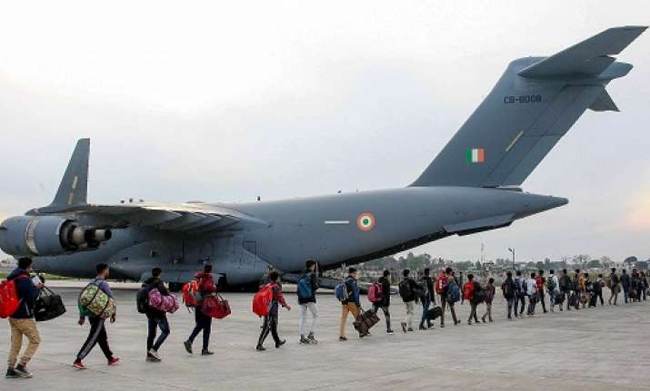 Stranded Kashmir bound passengers queue up to board a C-17
