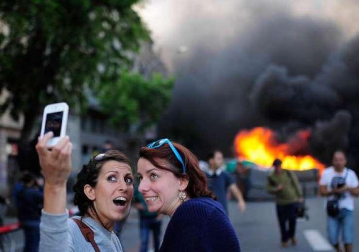 Women taking selfie with fire blaze in the backdrop. - India Tv
