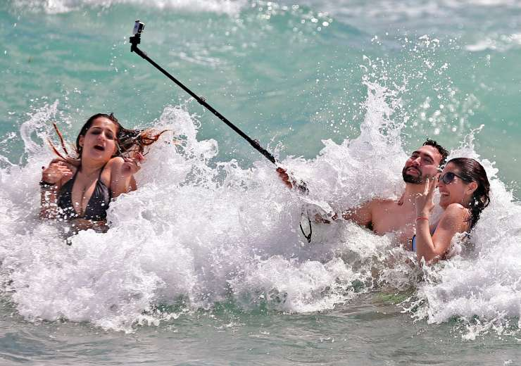 A couple clicking selfie while engulfed in water waves. - India Tv