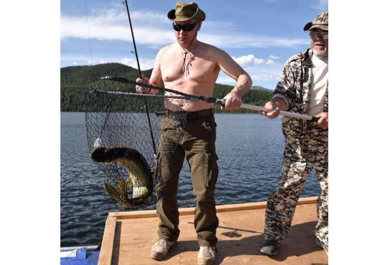 Putin holds his trophy catch while fishing during a mini-break in Siberian Tyva - India Tv