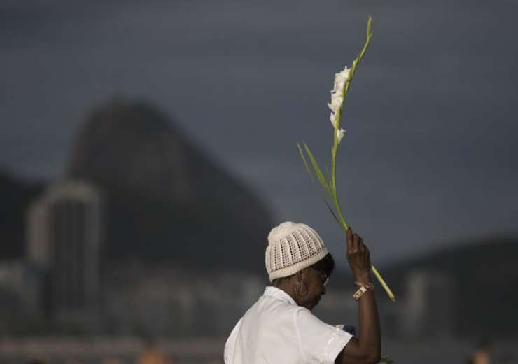 A woman offers flowers to Yemanja, goddess of the sea, for good luck in the coming year during New Year's Eve festivities in Rio de Janeiro, Brazil - India Tv