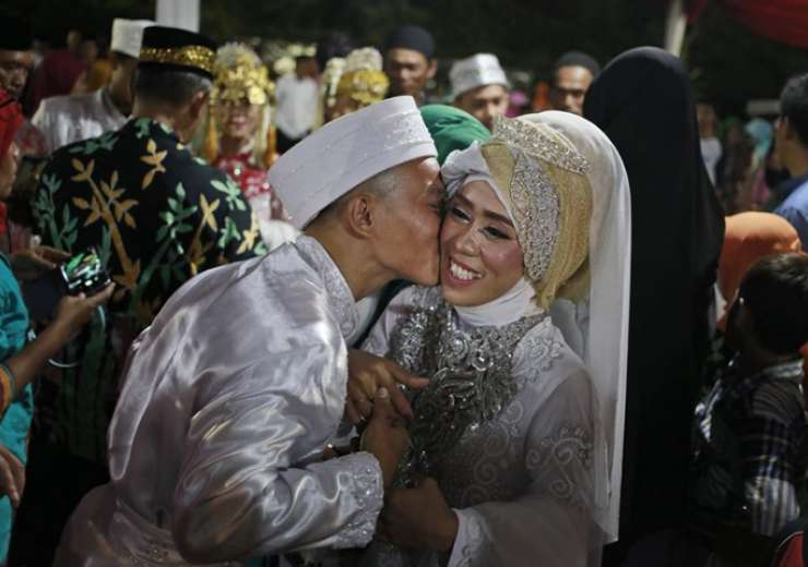 A groom kisses his bride during a mass wedding held in celebration of the New Year in Jakarta - India Tv