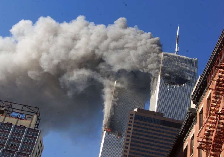 Smoke rises from the burning twin towers of the World Trade Center after hijacked planes crashed into the towers in New York City. - India Tv