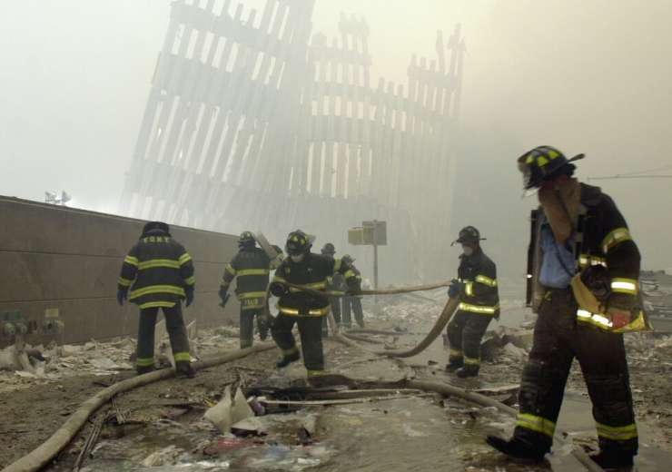 Firefighters work beneath the destroyed mullions after a terrorist attack on the twin towers in New - India Tv