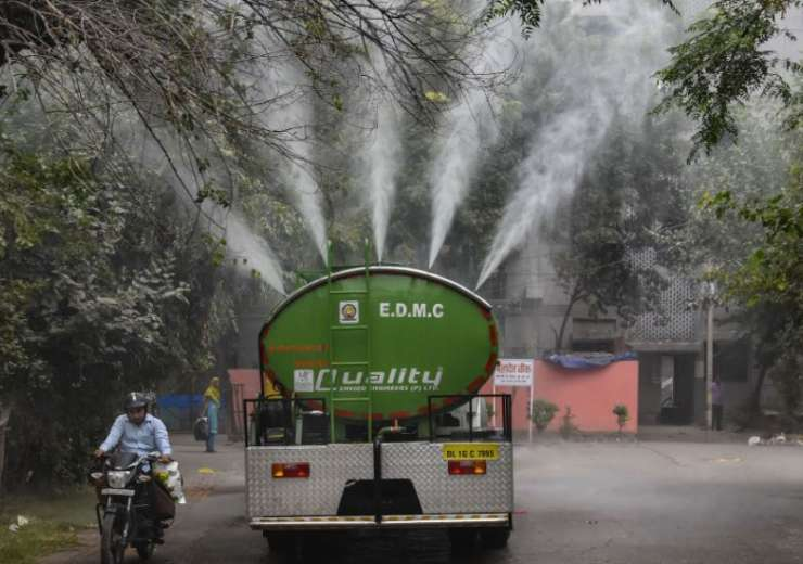 A water tanker belonging to East Delhi Municipal Corp sprays water to minimise pollution levels. - India Tv