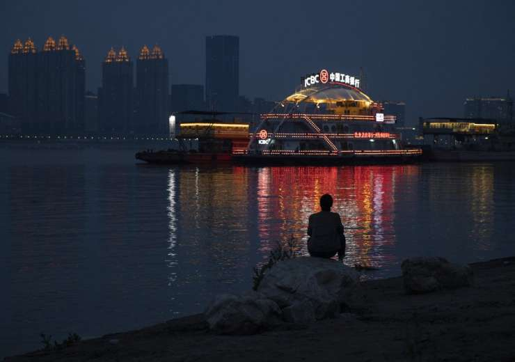 In this April 5, 2020, photo, a resident is silhouetted by lights reflected from a ferry along the Y - India Tv