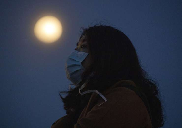 In this Monday, April 6, 2020, photo, a woman wearing a mask against the coronavirus looks up near t - India Tv