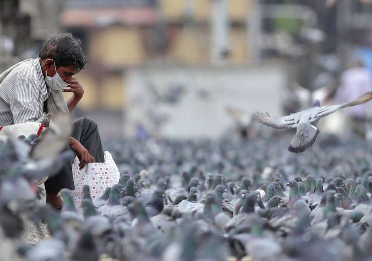Man wearing a face mask sits beside pigeons during a lockdown aimed at preventing the spread of new - India Tv