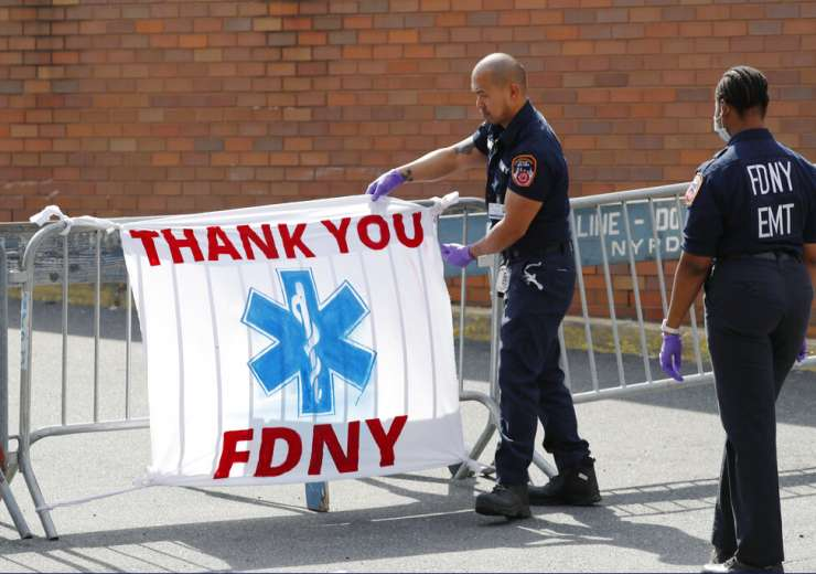 A colleague watches as a New York Fire Department Emergency Medical Technician (EMT) adjusts a