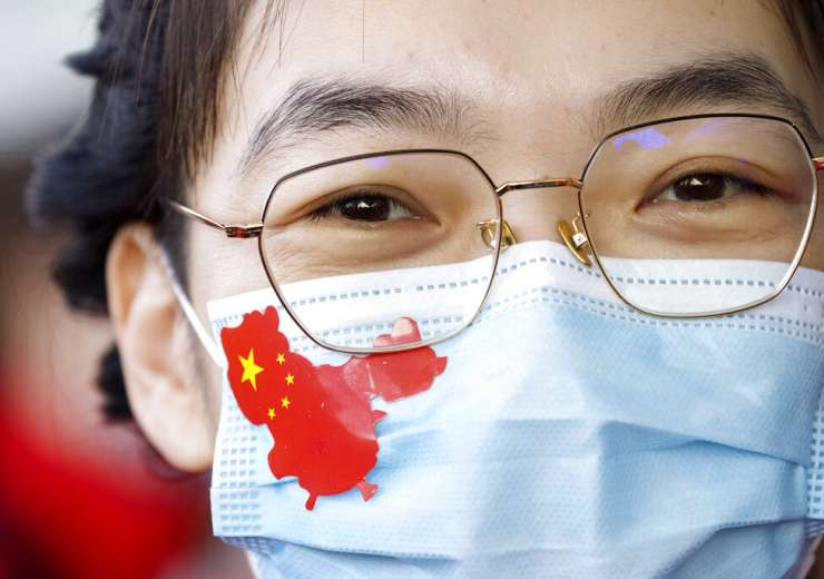 A medical worker from China's Jilin Province wears a sticker in the shape of China on her face mask - India Tv