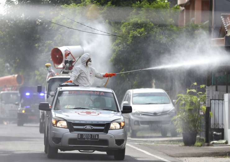 Members of Indonesian Red Cross stand on the back of a truck and spray disinfectant in an attempt to - India Tv