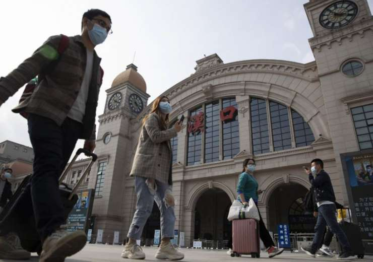 Wuhan: Travelers with their luggage walk past the Hankou railway station on the eve of its resuming - India Tv