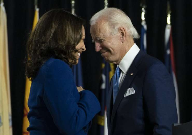 FILE - In this Aug. 12, 2020, file photo, Democratic presidential candidate former Vice President Joe Biden and his running mate Sen. Kamala Harris, D-Calif., pass each other as Harris moves to the podium to speak during a campaign event at Alexis Dupont High School in Wilmington, Del. Harris made history Saturday, Nov. 7, as the first Black woman elected as vice president of the United States, shattering barriers that have kept men — almost all of them white — entrenched at the highest levels of American politics for more than two centuries. (AP Photo/Carolyn Kaster, File)  - India Tv
