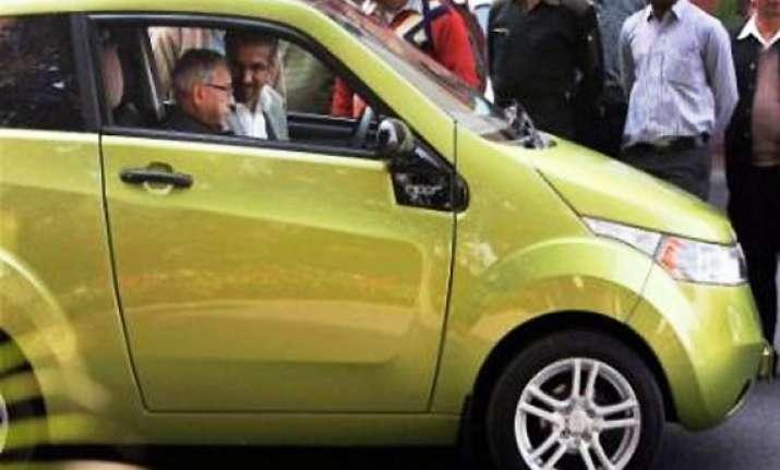 pranab sits in driving seat of mahindra electric car reva