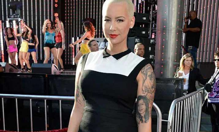 amber rose poses in revealing swimsuit