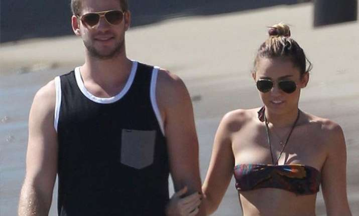 miley cyrus goes topless at beach