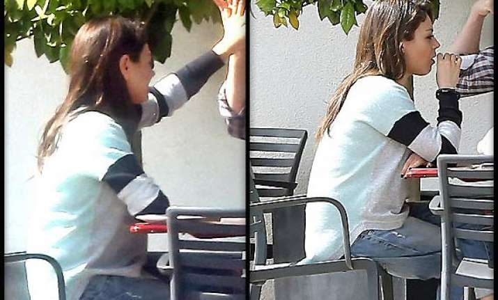 is mila kunis trying to hide baby bump opts for oversized