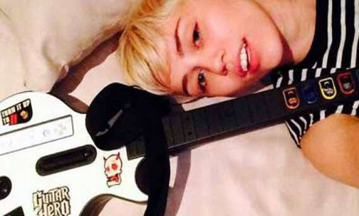 miley cyrus loves computer game guitar hero
