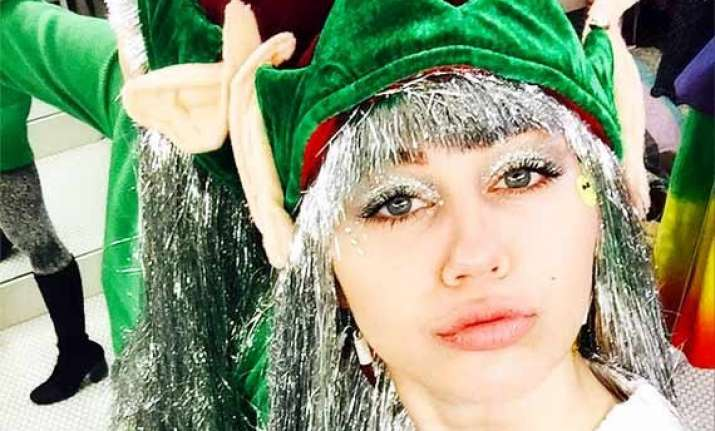 miley cyrus gears up for christmas with full elf costume