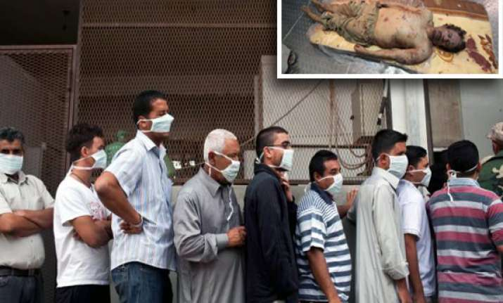hundreds queue up to watch gaddafi son s bodies in meat