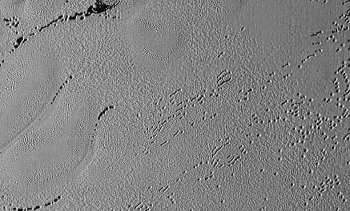 new image shows pluto s puzzling patterns pits