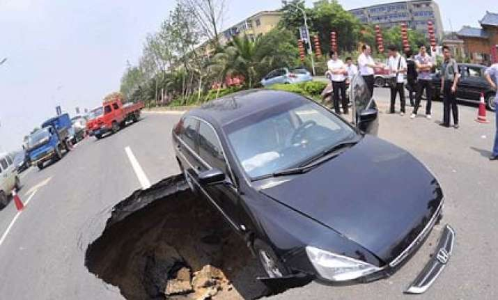 chinese driver has lucky escape as sinkhole swallows his car